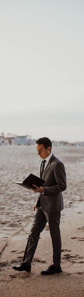 Jacob walking on the sand looking at his magic book