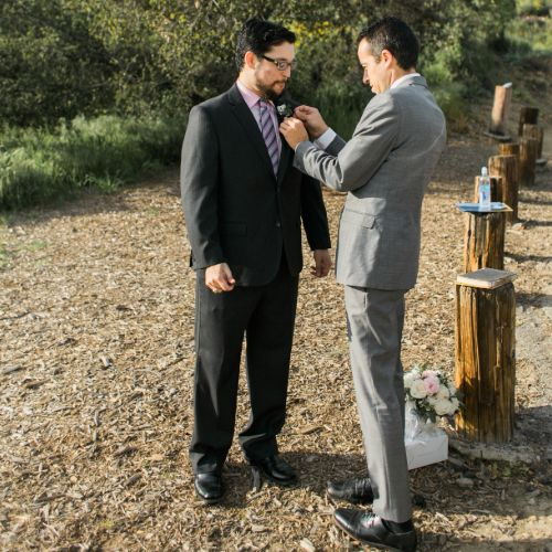 Jacob helping pin a flower on the suit of the groom